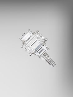 Love the emerald cut center stone offset by two side stones with diamond band. Three Stone Diamond Engagement Ring