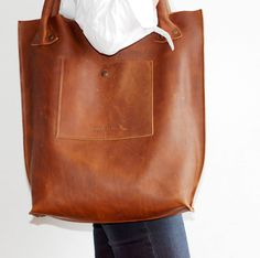 Leather Hobo cognac coloured. Robust and sturdy leather which shows marks and leather grain. Men love to carry and keep it since it has this raw yet elegant look and feel.
