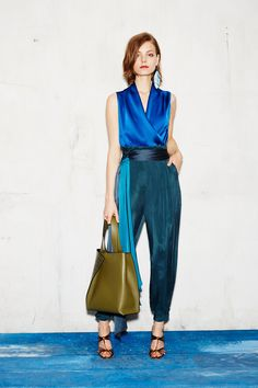 Paule Ka Resort 2017 Fashion Show. This outfit is so elegant and feminine. I love the contrast between the different shades of blue. The outfit is made of an electric blue sleeveless crepe blouse with gorgeous draping. The satin high waisted trousers come in a beautiful teal hue called Canard Green. The satin two tone belt mixes petrol blue to teal.