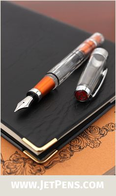 The transparent TWSBI Diamond 580AL Lava Fountain Pen features a faceted barrel, piston filling mechanism, and orange accents.