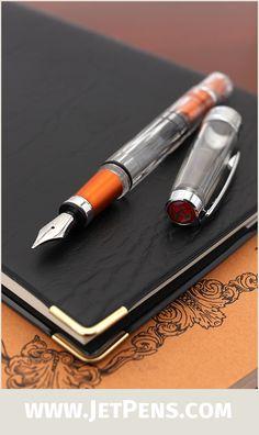 The transparent TWSBI Diamond 580AL Lava Fountain Pen features a faceted barrel, piston filling mechanism, and orange accents.