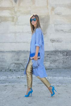 Street style star Clara Racz wearing a pinstriped shirtdress over gold pants with bold blue accessories