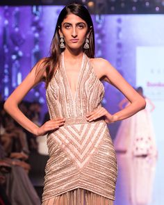 The Oyster Shell Gown The Oyster Shell gown exuberates the spirit of modern fashion. The gown is a melange of rich embroideries in summer sequins along with traditional sadi and kasab beautification. The timeless couture is comprises of a embellished halter neck, a sexy body gown silhouette followed by a heavily hand-done back trail. The cocktail creation is classic yet versatile with an avante-garde modern touch to it. Halter Neck, Sexy Body, Modern Fashion, Reflection, Trail, Shell, Cross Stitch, Cocktail, Bodycon Dress