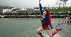 20150101 - Garota fantasiada pula no porto Carnlough, ao norte de Belfast, na Irlanda do Norte, durante comemorações de Ano-Novo, nesta quinta-feira (1º). PICTURE: Paul Faith/AFP