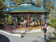 """The Dream Maker Carousel  © Bob & Sandy Cherot Date of picture: September, 2004  The """"Dream Maker"""" Carousel, located in the private garden of the Cherot Family home in Somers, Montana overlooks the Flathead Lake. It operates from May through September and is open to the public by reservation. Rides are free but donations to the local Volunteer Fire Department and Food Bank are accepted. Flathead Lake is visible in the background, along with some of Montana's Big Sky."""