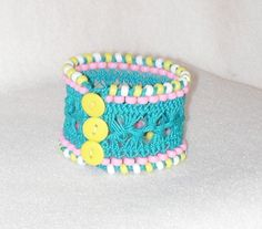 Turquoise hairpin lace bracelet accented with mini pony beads and a triple button closure. www.bonanza.com/booths/Nova55