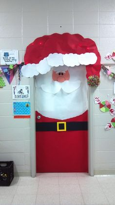 Create a colorful Santa classroom door display using red, white, and black construction paper.