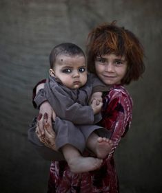 Refugee Children-Khalzarin Zirgul, 6 anos, segurando o seu primo, Zaman, de 3 meses.