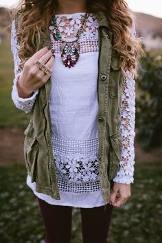 white lace tunic over burgundy jeans and topped with an olive green military style vest and statement necklace