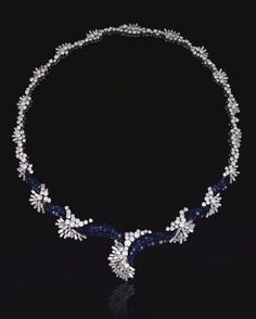 SAPPHIRE AND DIAMOND NECKLACE,  LATE 1960S.  Designed as a series of graduated abstract clusters set with baguette and brilliant-cut diamonds, highlighted at the front by stylised wave motifs close-set with calibré-cut sapphires, mounted in platinum,  signed Schilling.  length approximately 420mm,