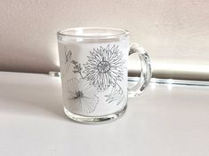 Floral Coffee and Tea Mug Beautiful glass coffee mug Ideal gift for her Gift mug Mug designs Mugs for you Floral design mug, unique gifts   This mug features a beautiful hand drawn graphic artwork created by Designer Irene Demetri.   Material: Clear Glass  Printing Method: Dye sublimation Sharp