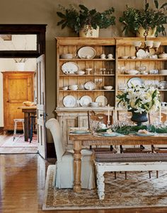 """The Reid home has great versatility, something Billy notes. """"We can have a formal party, or just throw a bunch of crawfish on the table."""" Here, a 19th-century English sideboard holds antique plates the couple has collected. Says Billy, """"Once you get that antiques bug, it's hard to stop.""""   - CountryLiving.com"""