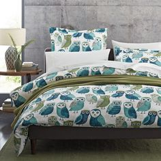 Artistic duvet cover inspired by mid-century illustrations. Displays wide-eyed owls in quirky shades of teal, aqua and olive.