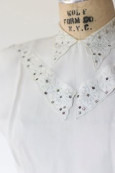 Beautiful 1940s blouse with embroidered collar and rhinestone details. Buttons up the back and has lovely pleats at waistline. Has small shoulder pads