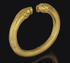 AN EAST GREEK GOLD BRACELET   CIRCA 5TH CENTURY B.C. .   Of penannular form, the solid hoop with lion-head terminals, with ears flattened against head, detailed facial features and incised mane