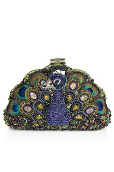 Show Off Mary Frances Designer Handbag. The proud and colorful display of the peacock is what Mary Frances handbags are about, as illustrated by this striking, hard-shell clutch. This half moon shaped hard case clutch is like a small treasure chest, adorned with Crystals and metal work thats as romantic as you are mysterious. A gorgeous arrangement of beads, stones, and peacock feathers, framed by an antique-metal shell, make this Show Off purse a showpiece. The padded back side is…