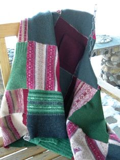 "A wonderful throw made of repurposed lambswool, merino wool, and wool. Made in shades of pine green and raspberry. You'll even find a pocket or two left from the sweaters on this one! Measures 45"" x 63"" . Machine washable.by Rosy Toes Designs"