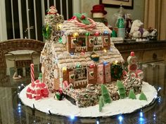 This no bake Gingerbread house was made by taping tgether boxes to form a house. I then cut out windows and a door and placed photos of my family in the cut outs. I placed battery operated miniature christmas lights on the inside to light it up. I then used royal icing to cover the walls with graham crackers and the rood with frosted mini wheats. I found multi colored mini lights and attached to edges of the roof and added all the candy elements.