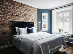 Bedroom with exposed brick wall. Small Cool Black Beauty In Göteborg - Gravity