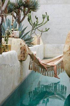 In einer Villa im Sommer eine Haengematte am Pool mit Kakteen