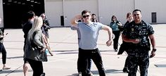 Taron Egerton waves bye to his costar Hugh Jackman as Hugh prepares for his flight in the cockpit of the F-16 - at the NAS Fort Worth Joint Reserve Base (20/02/2016)