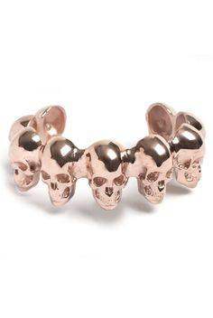 Memento Skull Bracelet in Rose Gold by LeiVanKash. Drawing inspiration from the still life Vanitas paintings and the genre of Memento Mori comes this beautiful skull bangle. Intricately hand-crafted skulls in bronze and plated in 2 Microns of 22 Karat rose gold with a bright polish finish thus striking the perfect balance between elegance and edge. Fits most wrist, can be gently moved to adjust to your size.