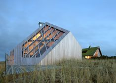 This timber-clad beach cabin is embedded into the sand dunes of a Dutch island, overlooking the North Sea.