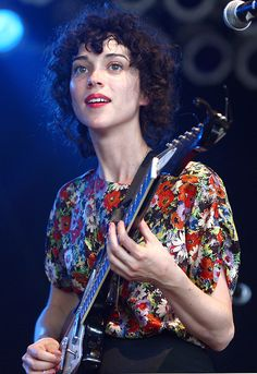 St. Vincent (Annie Clark). Guitar. Florals. Curls. Red lips.