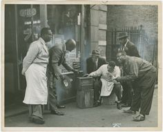 Harlem residents in front of shop listening to the radio, 1930s.  Photo credit: Schomburg Center for Research in Black Culture — in Harlem.