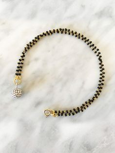 The Magic Ball mangalsutra bracelet fashionable and chic for the modern woman. Handmade by West Bengal artisans with 18K gold and real natural diamonds.