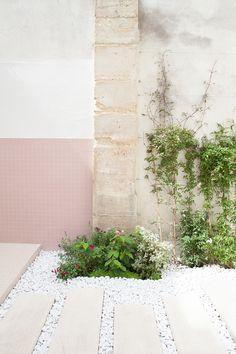 une bordure poreuse faite de galets et de plantes vivaces que l'on peut traverser grâce à des pas japonais en pierre