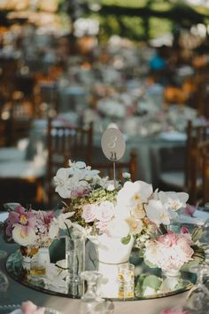 Dreamy wedding centerpiece - mirror topped with glass and porcelain vases filled with pastel flowers