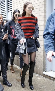 Bella Hadid. Black and red striped sweater+black denim skirt+black tights+black over the knee patent leather boots+black denim jacket+black handbag+golden choker+aviator sunglasses. Winter Casual Outfit 2017