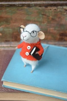 A highly-adorable felted studious mouse (who also looks like a sheep) with glasses and a book. Little Reader Mouse with Glasses by feltingdreams on Etsy.