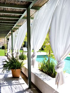 Breezy porch with white curtains to block sunlight and large swimming pool