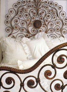 ironware bed and white fluffy bedding