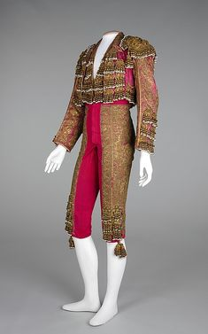 Suit (Toreador), J. Uriarte, fourth quarter 19th century, Spanish, silk, metal, glass, linen. The traditional traje de luces or suit of lights consists of fitted knee-length pants, vest, jacket, tie, pink stockings, and cape, and has remained unchanged for nearly two hundred years. The suits are quite expensive and take up to a month to create, with several seamstresses working in conjunction. The most traditional are densely embroidered in metallic gold and silver braid, beads, and sequins.