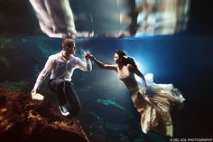 Bizarre trend: Newlyweds are choosing to pose underwater in their wedding outfits to celebrate entering married life - here a couple hold a pose in the waters of Mexicos Riviera Maya