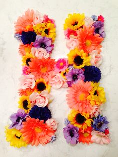 DIY FLOWER LETTER!  Hobby lobby wooden letter ($3.49) Artificial flowers ($1-$10)  I painted my wooden letter first a light pink color, then once it was dry I started putting the flowers on and hot gluing them! Fun and easy DIY!