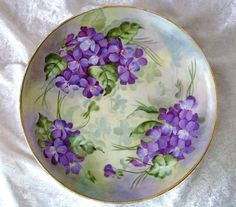 """Beautiful & Vibrant Haviland France 1900's Hand Painted """"Violets"""" 7-3/4"""" Plate. This plate has been exceptionally decorated with large groupings of life like and vibrant """"Violets"""" on stem and leaf against a background of extensive shadow leafing and background colors of light cream yellow, cream green, lavender and lavender gary. Gold gilding hasbeen added to the outer rim adding richness to this fabulous creation."""