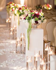 Pedestal flower arrangements lining the aisle at the wedding ceremony.