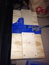 Kreg Jig is mounted on the hinged lid of a box with risers to provide stability for wider workpieces. Inside the box: dividers that go in dadoed slots on sides of box.