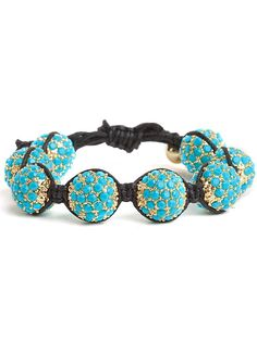 The bright colors of this chic, drawcord bracelet make it a great way to add a pop of color to daytime outfits. Eight gold-tone beads covered in acrylic turquoise pave detail are strung on a black leather cord.  Both ends of the leather cords are held together by leather clasps that allow you to easily adjust the sizes of the bracelets by pulling the cords looser or tighter.