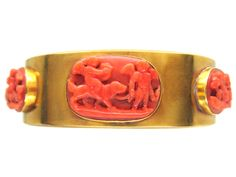 A most unusual Coral and gold bangle which has been set with Neo-Classical carved coral oval sections with cherubs a dog and dolphins. On the back section there are four round flower head carved coral sections. It is most attractive and was made circa Turquoise Jewelry, Gemstone Jewelry, Gold Jewelry, Jewellery, Ancient Jewelry, Antique Jewelry, Natural Stone Jewelry, Art Carved, Coral