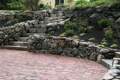 Clay bricks with natural stones and reclaimed granite steps & landscape lights make this historic looking patio in North Andover