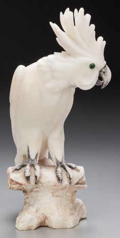 A CARVED ALABASTER AND GLASS FIGURE: COCKATOO, 20th Century.
