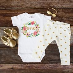 """There are multiple options on this listing. Note that Moccasins are ONLY available in sizes 6-12, and 12-18 months.This Glitter Gold """"One"""" Birthday Onesie with watercolor wreath is so cute! The outfit is made perfect with an adorable gold foil dot leggings fabric. You also have the option to add mocs and a knotted leather bow. Bodysuit Size Chart:Size ____________Height(in)______Weight(lbs.)6-12 Mo.----------------27-30----------------18-2212-18 Mo.--------------30-34---------------..."""