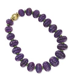 David WEBB - An Amethyst  and Enamel Necklace.  Designed as a graduated series of large fluted Amethyst beads, spaced by green Enamel rondelles, to the hammered 18k Gold boule clasp,18¼ ins. Signed Webb for David Webb •$17,500USD