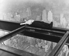 A workman takes a siesta on a girder during the building of Radio City, the city of New York spread out below, circa 1933.