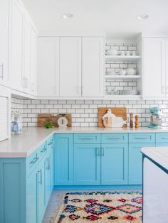 What once was a dark, dreary, frankly depressing and dated space is now an open, refreshing kitchen full of life and joy-inducing design moments. With new colorful cabinets, a touch of vintage, a contrasting backsplash and a bright rug, this kitchen is certainly no longer drab.